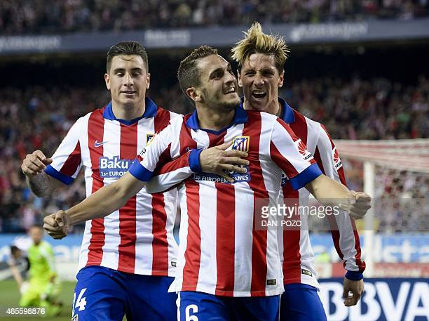 Atletico Madrid's midfielder Koke celebrates with teammates after scoring during the Spanish league football match Atletico Madrid vs Valencia CF at...