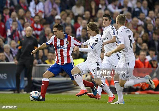 Atletico Madrid's midfielder Koke vies with Real Madrid's Croatian midfielder Luka Modric Real Madrid's Colombian midfielder James Rodriguez and Real...