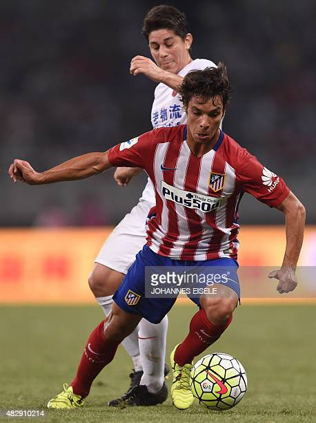 Atletico Madrid's midfielder Oliver Torres and Shanghai's Argentinian forward Dario Conca vie for the ball during a friendly football match between...