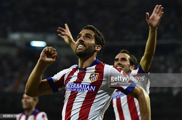 Atletico Madrid's midfielder Raul Garcia celebrates after scoring during the Spanish Supercup firstleg football match Real Madrid CF vs Club Atletico...