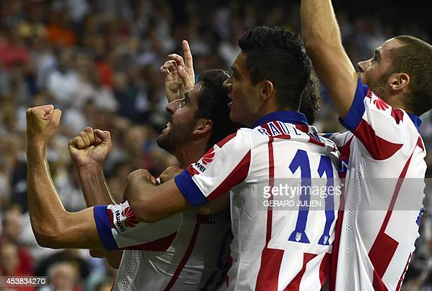 Atletico Madrid's midfielder Raul Garcia celebrates with his teammates after scoring during the Spanish Supercup firstleg football match Real Madrid...