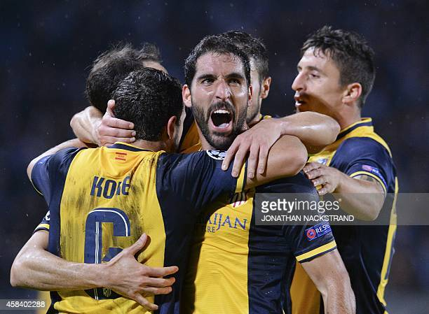 Atletico Madrid's midfielder Raul Garcia celebrates with his teammates after scoring during the UEFA Champions League secondleg Group A football...