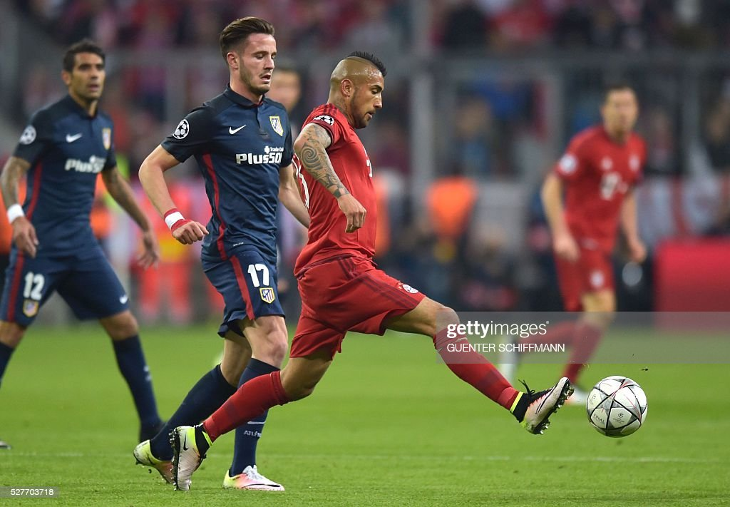 Atletico Madrid's midfielder Saul Niguez (2ndL) and Bayern Munich's Chilean midfielder Arturo Vidal fight for the ball during the UEFA Champions League semi-final, second-leg football match between FC Bayern Munich and Atletico Madrid in Munich, southern Germany, on May 3, 2016. / AFP / GUENTER