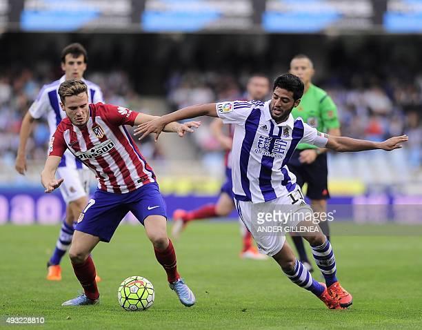 Atletico Madrid's midfielder Saul Niguez vies with Real Sociedad's Mexican forward Carlos Vela during the Spanish league football match Real Sociedad...