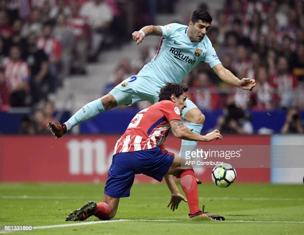 Atletico Madrid's Montenegrin defender Stefan Savic vies with Barcelona's Uruguayan forward Luis Suarez during the Spanish league football match Club...