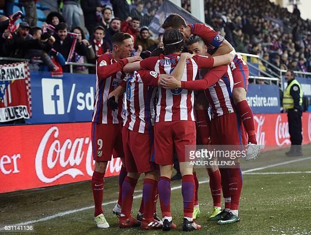 Atletico Madrid's players celebrate after midfielder Saul Niguez scored his team's first goal during the Spanish league football match SD Eibar vs...