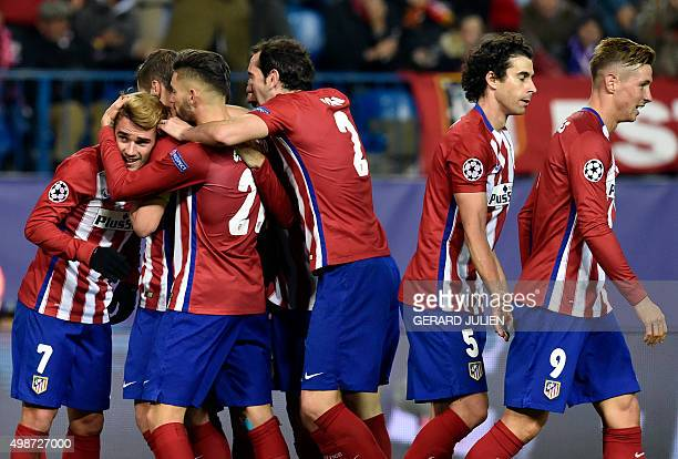 Atletico Madrid's players congratulate teammate French forward Antoine Griezmann after scoring a second goal during the UEFA Champions League Group C...