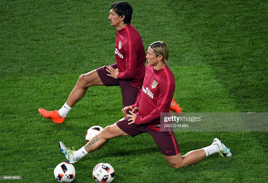 Atletico Madrid's players Fernando Torres (R) and Stefan Savic (L) stretch during a football training session at AAMI Park in Melbourne on July 28, 2016. / AFP / SAEED