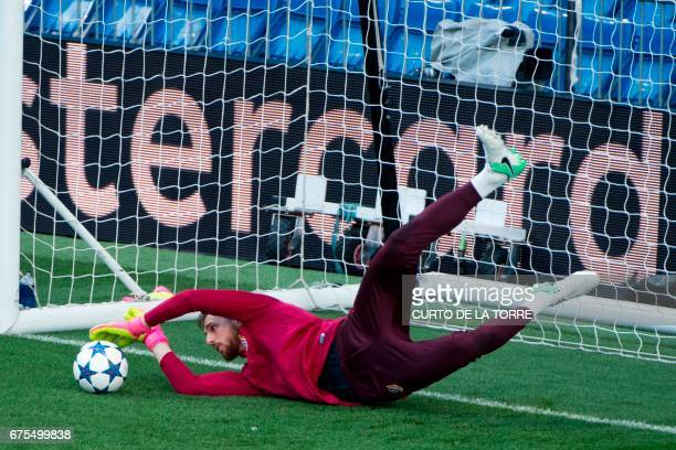 Atletico Madrid's Slovenian goalkeeper Jan Oblak dives and stops a ball during a training session at Santiago Bernabeu stadium in Madrid on May 1 on...