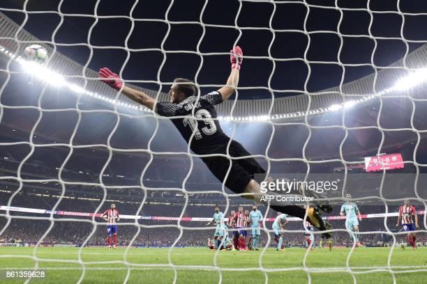 Atletico Madrid's Slovenian goalkeeper Jan Oblak dives for the ball during the Spanish league football match Club Atletico de Madrid vs FC Barcelona...