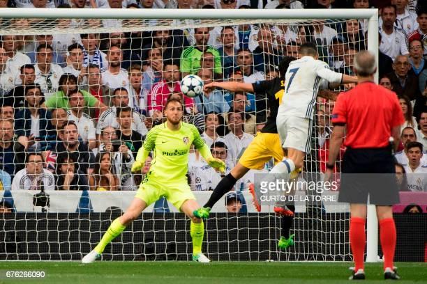 Atletico Madrid's Slovenian goalkeeper Jan Oblak eyes the ball as Real Madrid's Portuguese forward Cristiano Ronaldo heads to score during the UEFA...