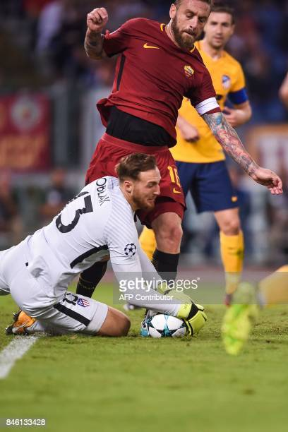 Atletico Madrid's Slovenian goalkeeper Jan Oblak grabs a ball in the feet of Roma's midfielder Daniele De Rossi during the UEFA Champions League...