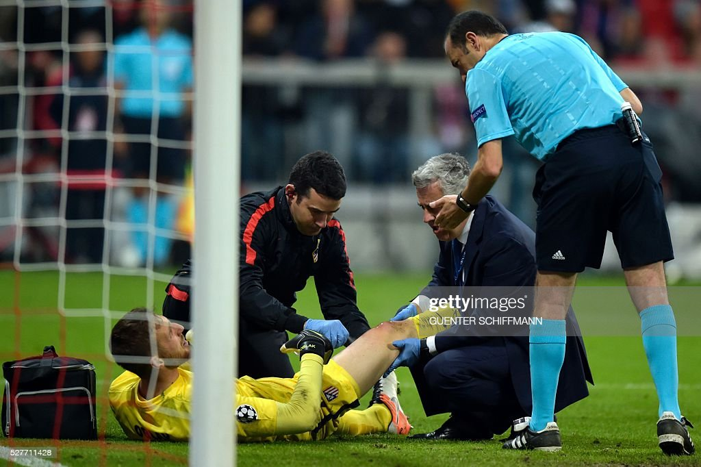 Atletico Madrid's Slovenian goalkeeper Jan Oblak (L) is helped by medical staff while lying on the pitch during the UEFA Champions League semi-final, second-leg football match between FC Bayern Munich and Atletico Madrid in Munich, southern Germany, on May 3, 2016. / AFP / GUENTER