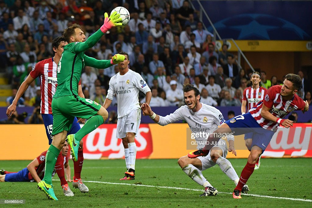 Atletico Madrid's Slovenian goalkeeper Jan Oblak (L) makes a save during the UEFA Champions League final football match between Real Madrid and Atletico Madrid at San Siro Stadium in Milan, on May 28, 2016. / AFP / GERARD