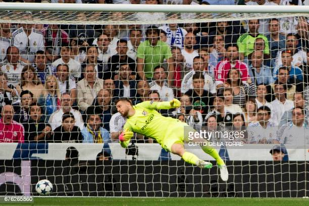 Atletico Madrid's Slovenian goalkeeper Jan Oblak misses to stop the ball after Real Madrid's Portuguese forward Cristiano Ronaldo scored during the...