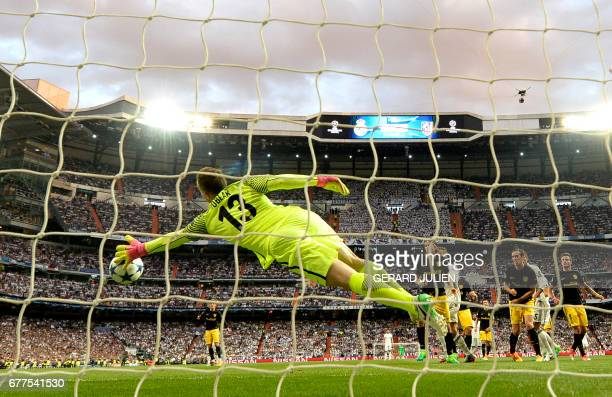 Atletico Madrid's Slovenian goalkeeper Jan Oblak stops the ball during the UEFA Champions League semifinal first leg football match Real Madrid vs...