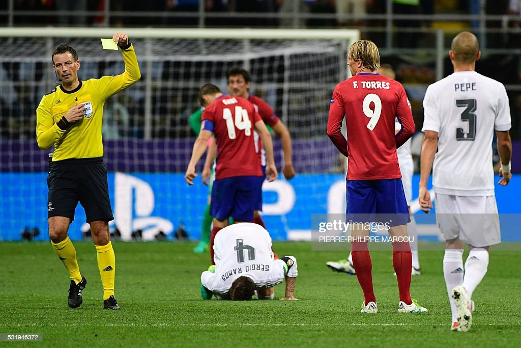 Atletico Madrid's Spanish forward Fernando Torres (2nd R) reveives a yellow card by English referee Mark Clattenburg as Real Madrid's Spanish defender Sergio Ramos lies on the ground, during the UEFA Champions League final football match between Real Madrid and Atletico Madrid at San Siro Stadium in Milan, on May 28, 2016. / AFP / PIERRE