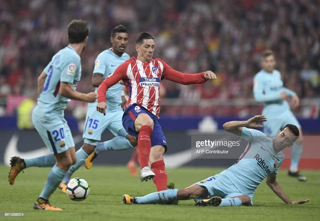 Atletico Madrid's Spanish forward Fernando Torres (3L) vies with Barcelona's Spanish midfielder Sergio Busquets (R) during the Spanish league football match Club Atletico de Madrid vs FC Barcelona at the Wanda Metropolitano stadium in Madrid on October 14, 2017. /