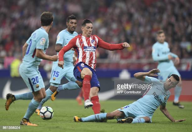 Atletico Madrid's Spanish forward Fernando Torres vies with Barcelona's Spanish midfielder Sergio Busquets during the Spanish league football match...