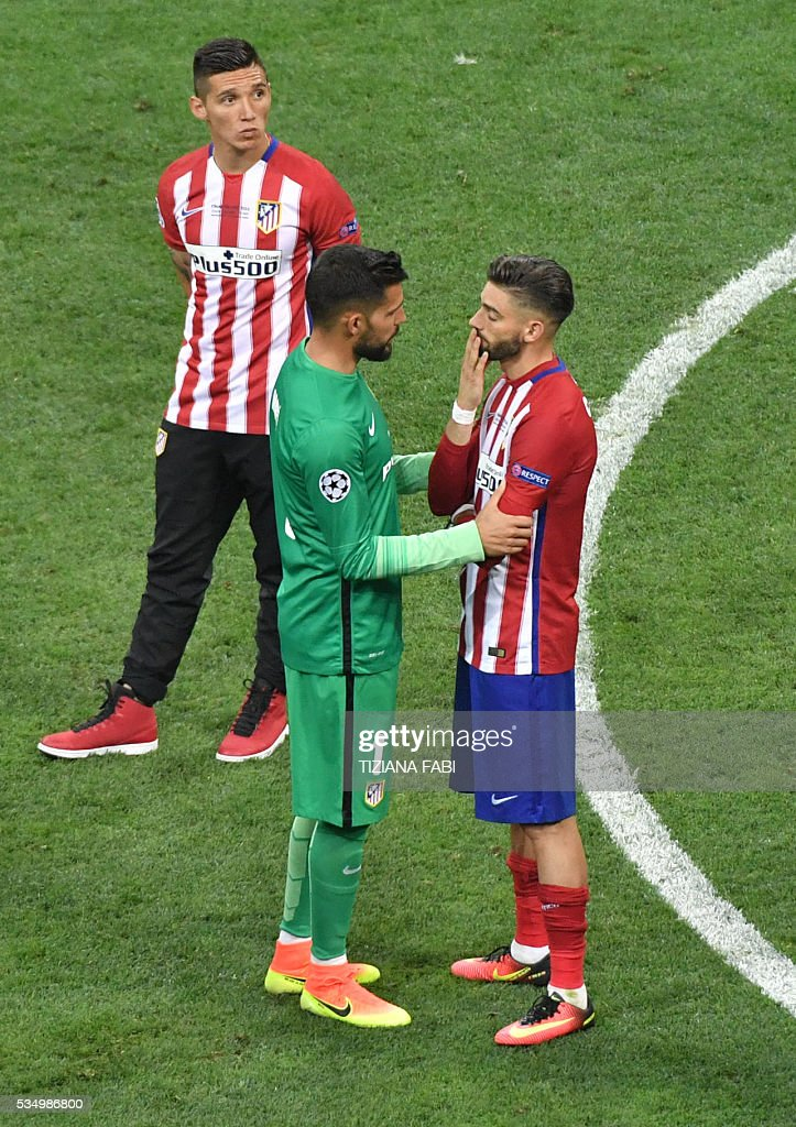Atletico Madrid's Spanish goalkeeper Miguel Angel Moya (L) consols Atletico Madrid's Belgian forward Yannick Ferreira Carrasco after loosing to Real Madrid in the UEFA Champions League final football match at the San Siro Stadium in Milan, on May 28, 2016. Real Madrid beat city rivals Atletico for the second time in three years to win the Champions League for the 11th time. / AFP / TIZIANA