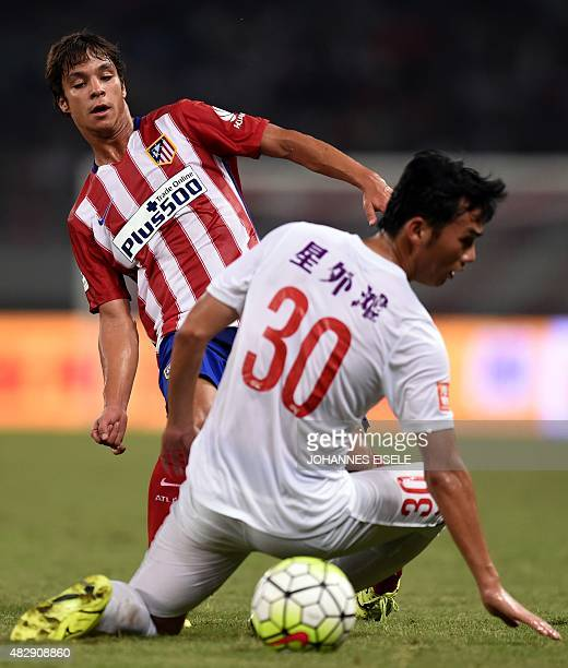 Atletico Madrid's Spanish midfielder Oliver Torres makes a pass through Shanghai's Chinese forward Zhengrong Zhu during a friendly football match...
