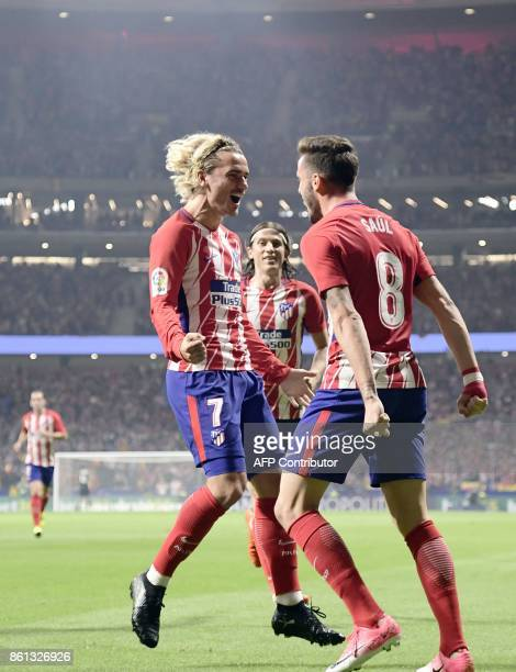 Atletico Madrid's Spanish midfielder Saul Niguez celebrates a goal with Atletico Madrid's French forward Antoine Griezmann during the Spanish league...