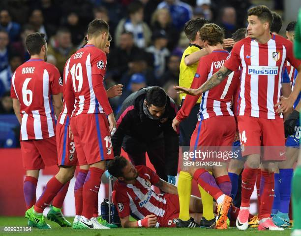 Atletico Madrid's Spanish midfielder Saul Niguez lays on the pitch follwing a challenge with Leicester City's Algerian midfielder Riyad Mahrez during...