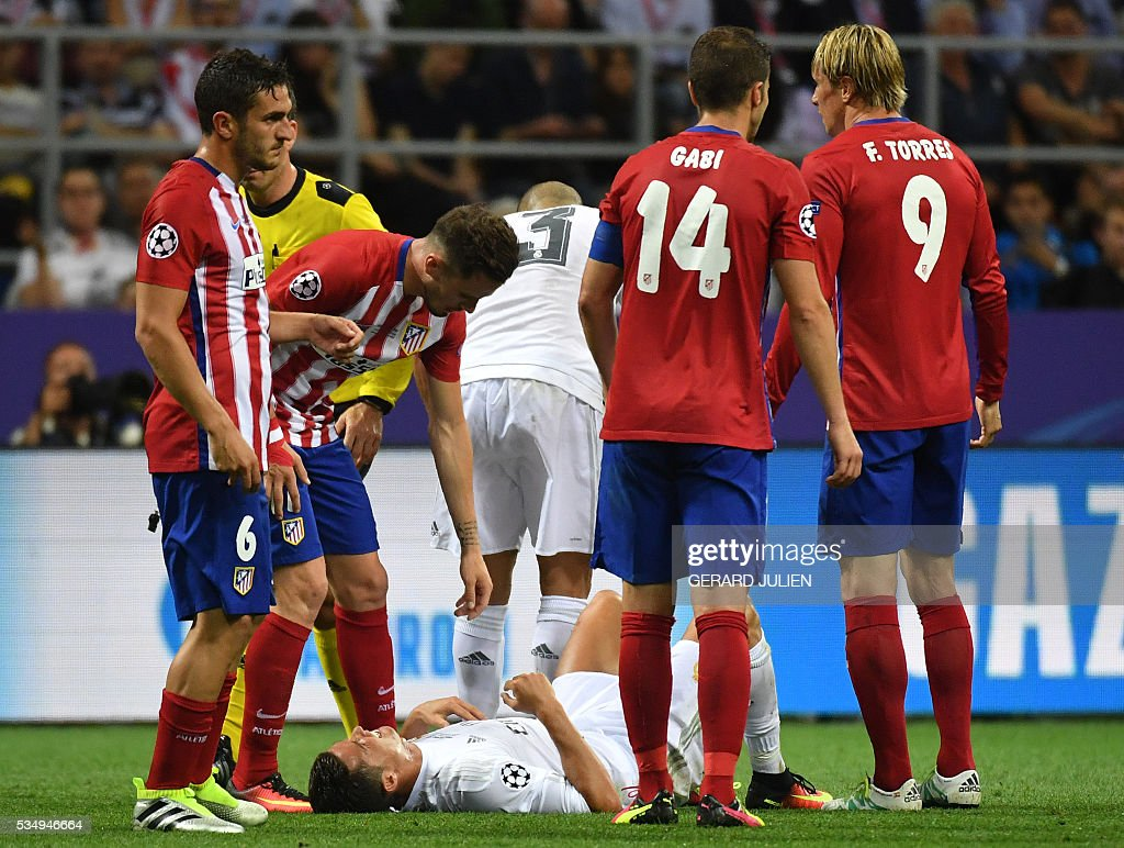 Atletico Madrid's Spanish midfielder Saul Niguez (2ndL) speaks with Real Madrid's Portuguese forward Cristiano Ronaldo (C) lying on the ground, surrounded by Atletico Madrid's Spanish midfielder Koke (L), Atletico Madrid's Spanish midfielder Gabi (2ndR) and Atletico Madrid's Spanish forward Fernando Torres (R) during the UEFA Champions League final football match between Real Madrid and Atletico Madrid at San Siro Stadium in Milan, on May 28, 2016. / AFP / GERARD