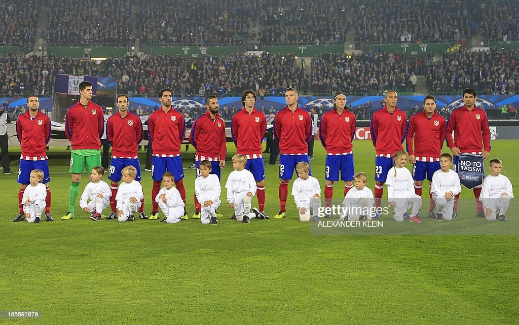 Atletico Madrid's team players (L-R) midfielder Mario Suarez, Belgian goalkeeper Thibaut Courtois, midfielder Juanfran, midfielder Raul Garcia, Turkish midfielder Arda Turan, Portuguese midfielder Tiago Mendes, Belgian defender Tobias Alderweireld, Brazilian defender <a gi-track='captionPersonalityLinkClicked' href=/galleries/search?phrase=Filipe+Luis&family=editorial&specificpeople=3941966 ng-click='$event.stopPropagation()'>Filipe Luis</a>, Brazilian defender Joa Miranda de Souza, midfielder Koke and Brazilian forward Diego da Silva Costa poses for a team picture with the with the UEFA 'No to Racism' flag, ahead of the start of a group stage UEFA Champions League football match between Austria Wien and Atletico de Madrid on October 22, 2013 at the Ernst Happel stadium in Vienna. Atletico Madrid's won 3-0. AFP PHOTO / ALEXANDER KLEIN