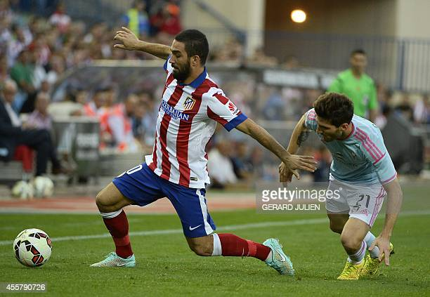 Atletico Madrid's Turkish midfielder Arda Turan vies with Celta Vigo's defender Carles Planas during the Spanish league football match Club Atletico...