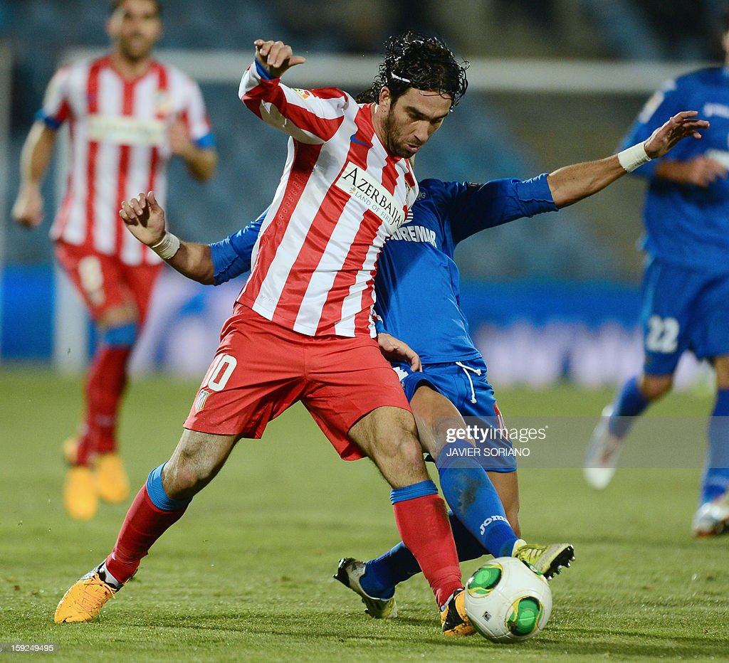Atletico Madrid's Turkish midfielder Arda Turan (L) vies with Getafe's midfielder Jaime Gavilan (R) during the Spanish Copa del Rey (King's Cup) round of 16, second leg, football match Getafe vs Atletico de Madrid at the Coliseum Alfonso Perez stadium in Getafe on January 10, 2013. AFP PHOTO / JAVIER SORIANO