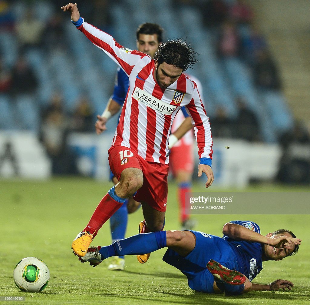 Atletico Madrid's Turkish midfielder Arda Turan (top) vies with Getafe's midfielder Xavier Torres during the Spanish Copa del Rey (King's Cup) round of 16, second leg, football match Getafe vs Atletico de Madrid at the Coliseum Alfonso Perez stadium in Getafe on January 10, 2013. AFP PHOTO / JAVIER SORIANO