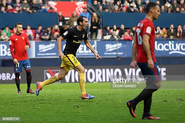 Atletico Madrid's Uruguayan defender Diego Godin celebrates after scoring during the Spanish league football match CA Osasuna vs Club Atletico de...