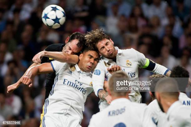 TOPSHOT Atletico Madrid's Uruguayan defender Diego Godin heads the ball with Real Madrid's Brazilian midfielder Casemiro and Real Madrid's defender...