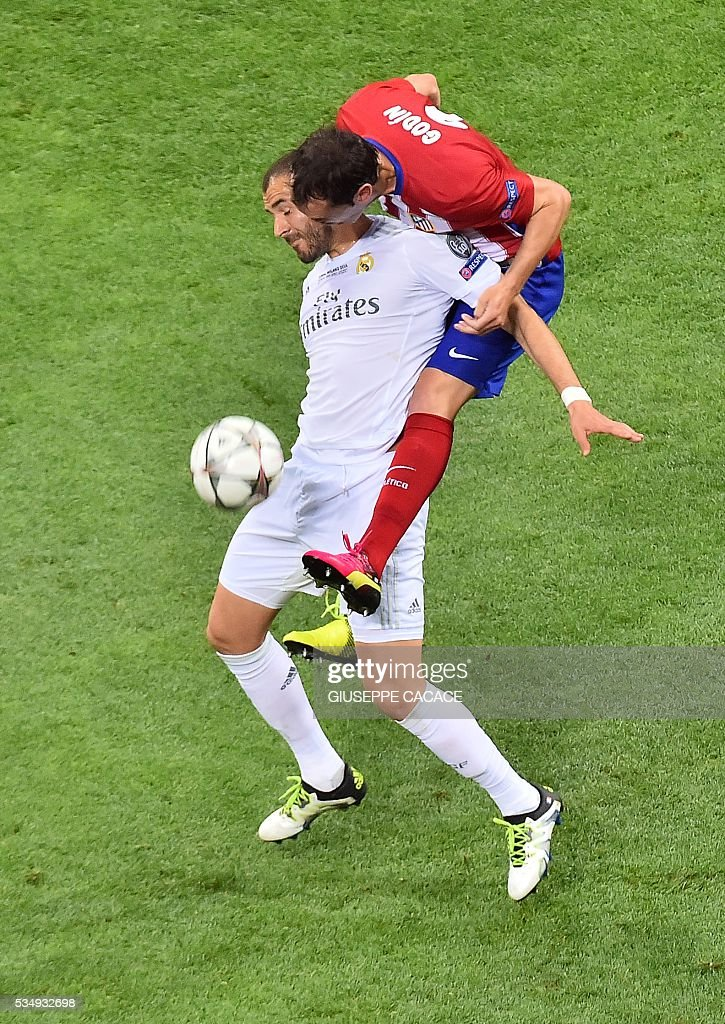 Atletico Madrid's Uruguayan defender Diego Godin (top) vies for the ball with Real Madrid's French forward Karim Benzema during the UEFA Champions League final football match between Real Madrid and Atletico Madrid at San Siro Stadium in Milan, on May 28, 2016. / AFP / GIUSEPPE