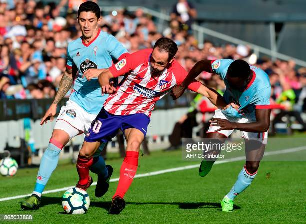 Atletico Madrid's Uruguayan defender Diego Godin vies with Celta Vigo's Danish midfielder Pione Sisto and teammate Chilean midfielder Pablo Hernandez...