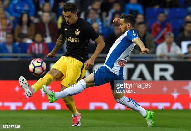 Atletico Madrid's Uruguayan defender Diego Godin vies with Espanyol's midfielder Victor Sanchez during the Spanish league football match RCD Espanyol...