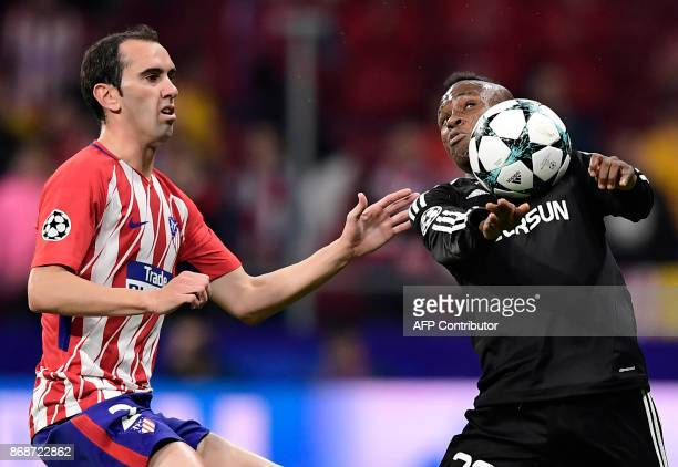 Atletico Madrid's Uruguayan defender Diego Godin vies with Qarabag's Haitian midfielder Donald Guerrier during the UEFA Champions League football...