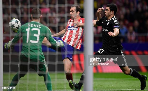 Atletico Madrid's Uruguayan defender Diego Godin vies with Qarabag's Azerbaijani forward Ramil Sheydaev during the UEFA Champions League football...