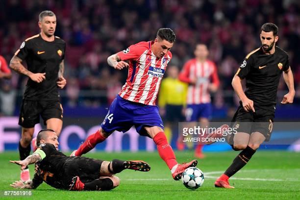 Atletico Madrid's Uruguayan defender Jose Gimenez challenges Roma's Belgian midfielder Radja Nainggolan Roma's Croatian defender Aleksandar Kolarov...