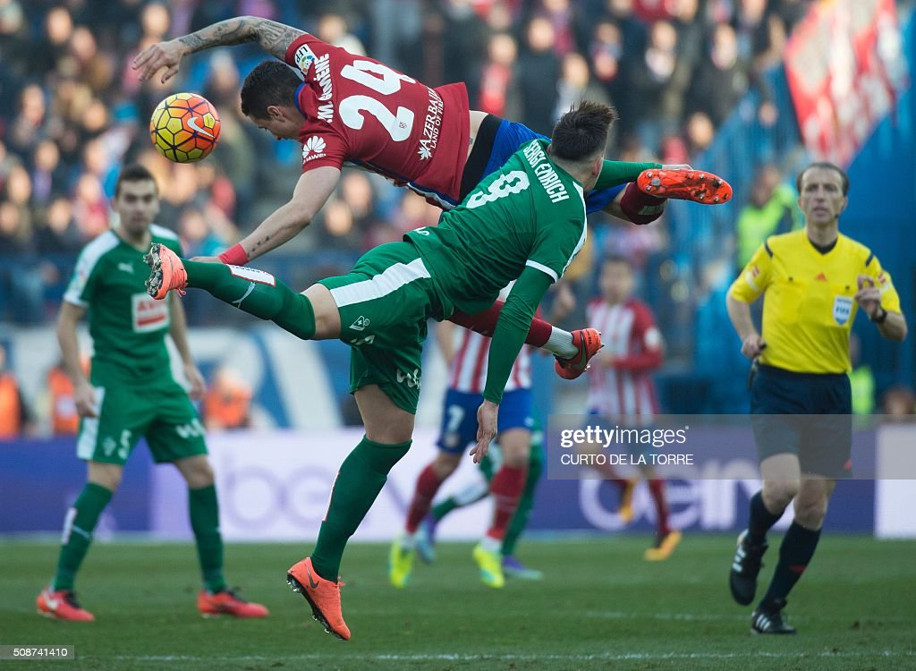 Atletico Madrid's Uruguayan defender Jose Maria Gimenez (L) jumps for the ball with Eibar's forward Sergi Enrich during the Spanish league football match Club Atletico de Madrid vs SD Eibar at the Vicente Calderon stadium in Madrid on February 6, 2016. AFP PHOTO / CURTO DE LA TORRE / AFP / CURTO DE LA TORRE