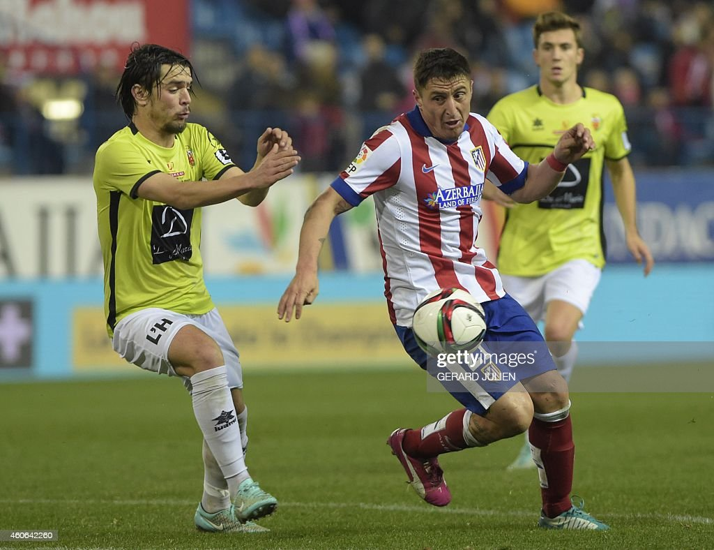 Atletico Madrid's Uruguayan forward Cristian Rodriguez (R) vies with Hospitalet's midfielder Alex Barrera during the Spanish Copa del Rey (King's Cup) round of 32 second leg football match Club Atletico de Madrid vs CE L'Hospitalet at the Vicente Calderon stadium in Madrid on December 18, 2014. AFP PHOTO/ GERARD JULIEN
