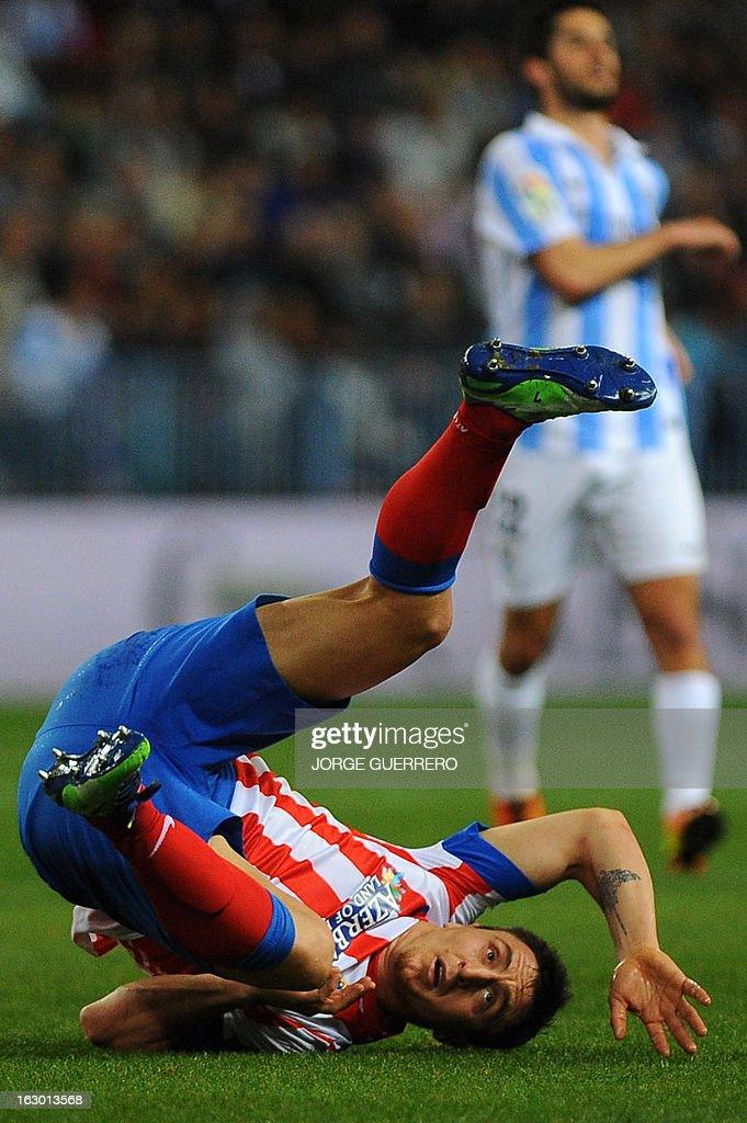 Atletico Madrid's Uruguayan midfielder Cristian Rodriguez falls during the Spanish league football match Malaga CF vs Atletico de Madrid on March 3, 2013 at Rosaleda stadium in Malaga.