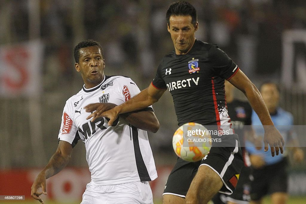 Atletico Mineiro's Jo (L) vies for the ball with of Colo Colo's Cristian Vilches (R) during their Copa Libertadores football match at Monumental stadium in Santiago, Chile, on February 18, 2015. AFP PHOTO /Claudio Reyes