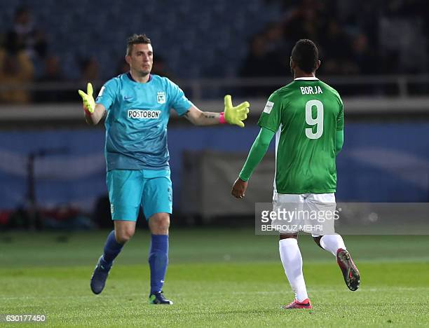 CORRECTION Atletico Nacional's forward Miguel Borja celebrates with goalkeeper Franco Armani after scoring the last penalty in the penalty shootout...