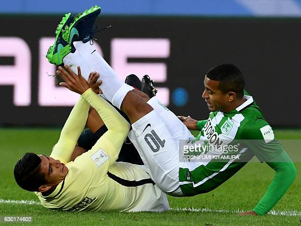 TOPSHOT Atletico Nacional's midfielder Macnelly Torres falls on the pitch with Club America's defender Erik Pimentel during the Club World Cup...