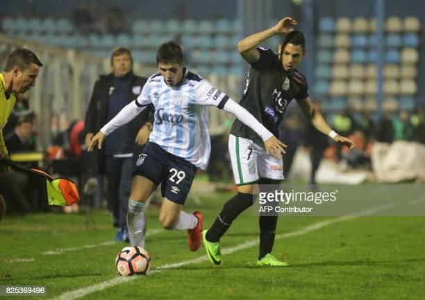Atletico Tucuman's Gabriel Risso vies for the ball with Oriente Petrolero's Jose Meza during their Copa Sudamericana 2017 football match at the Jose...