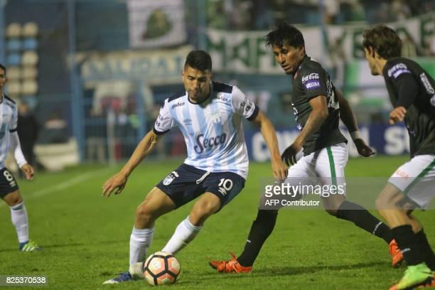 Atletico Tucuman's Gervasio Nunez vies for the ball with Oriente Petrolero's Helmut Gutierrez and Deni Bejarano Molina during their Copa Sudamericana...