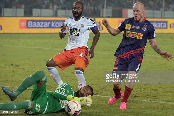 AtleticodeKolkata's forward Iain Edward Hume vies for the ball with FC Pune City goalkeeper Arindam Bhattacharja during the Indian Super League...