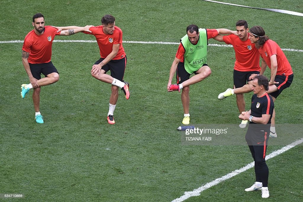 Atletico's players stretch during a training session at the San Siro Stadium in Milan, on May 27, 2016, on the eve of the UEFA Champions League final foobtall match between Real Madrid and Atletico Madrid. / AFP / TIZIANA